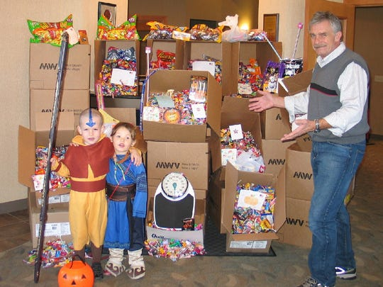 Dr. Mike Schneidler and Pewaukee Dental are in their 10th year of collecting candy to send care packages to troops stationed overseas. In this photo, Schneidler stands with Jackson Scheufele and Indica Scheufele at a previous collection.