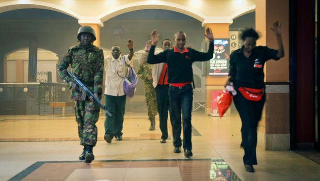 Civilians who had been hiding inside the Westgate Mall in Nairobi during the standoff exit the scene Sept. 21. 2013.  The extremist group Al-Shabab live-tweeted about this mall siege in Kenya.