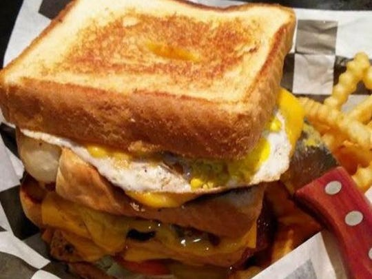 The Dump Truck Burger at Ride's Bar & Grill in Fort Dodge is one of its specialties -- three 6-ounce beef patties layered between four thick slices of Texas toast, six slices of bacon, cheese and a fried egg, served with fries.