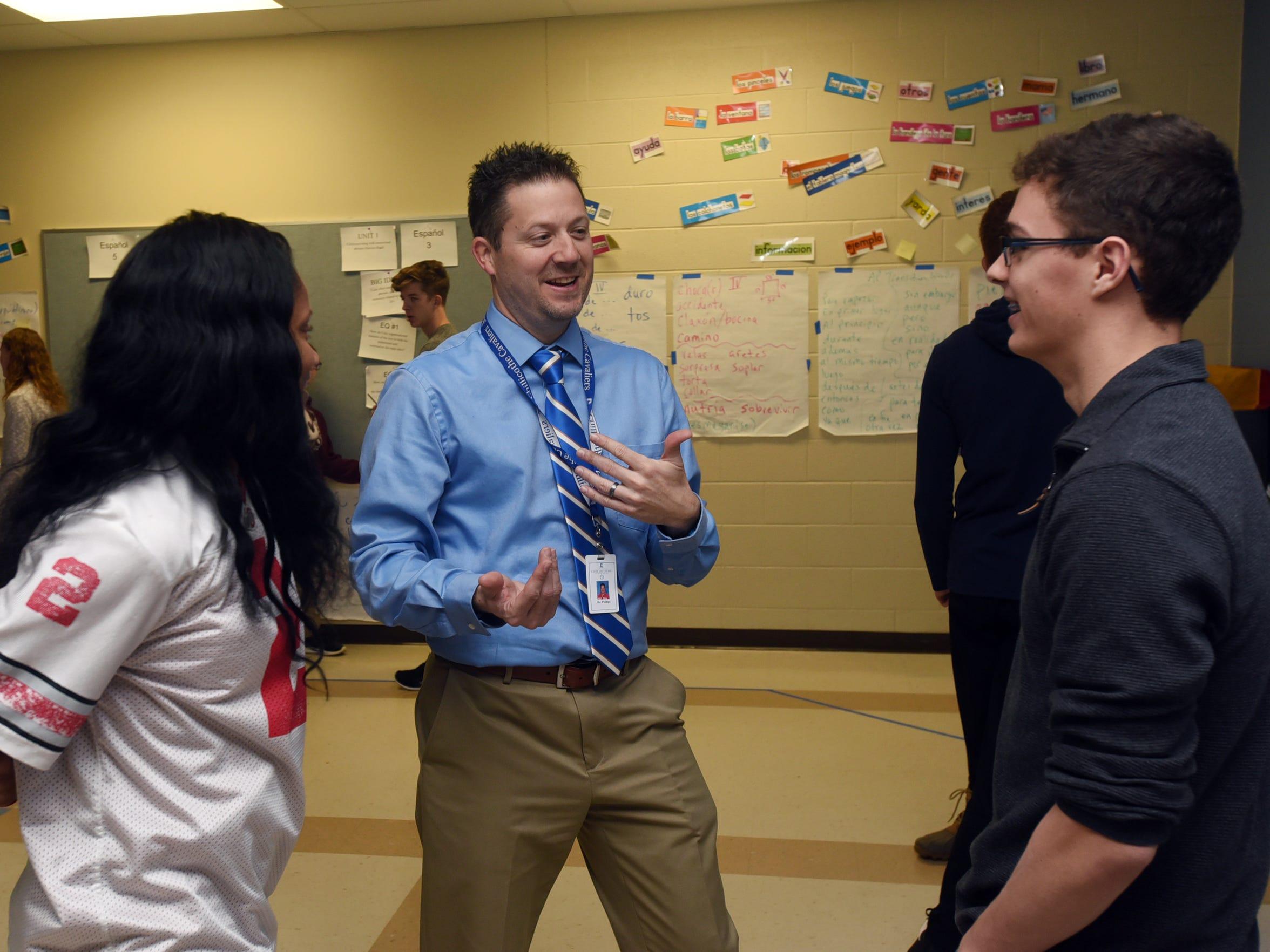 Greg Phillips, center, talks to students in Spanish