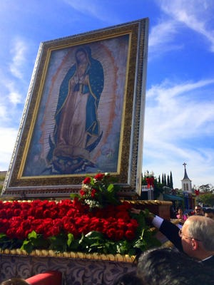 Archbishop José H. Gomez places a bouquet of red roses at the feet of the image of Our Lady of Guadalupe during the Our Lady procession and Mass in East Los Angeles. The procession was held Dec. 6, 2015. This year, the tour will stop at several Ventura County parishes.