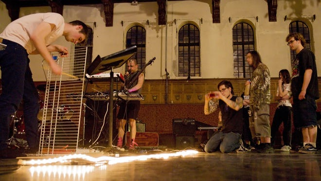 Corey Mahaney, left, plays a piece of shelving as he and Bubba Crumrine, background, of Genital Holograms open an 2010 Ithaca Underground show at the Community School of Music and Arts.