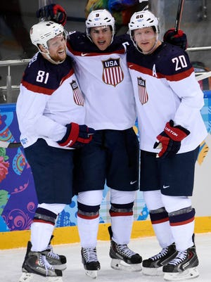 USA forward Zach Parise (9) celebrates with forward Phil Kessel (81) and defenseman Ryan Suter (20) after scoring a goal in the second period against Czech Republic in the men's ice hockey quarterfinals during the Sochi 2014 Olympic Winter Games at Shayba Arena.