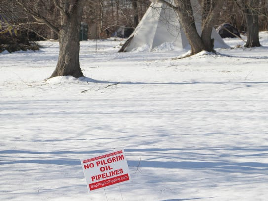 Tents and tepees are a backdrop to signs protesting