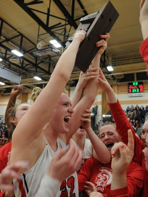 Bridgewater-Raynham's Shay Bollins hoists the Division 1 South sectional trophy at the conclusion of their game versus Needham, on Saturday, March 7, 2020.