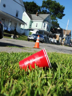 FILE - This red plastic party cup was left on the grass in the aftermath of a block party on Myrtle Street on July 20, 2017.