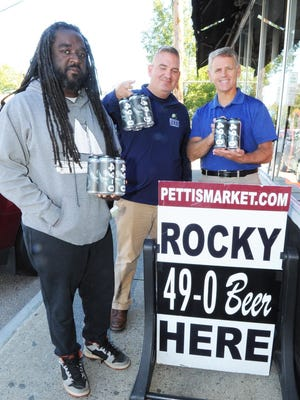 Brockton Beer Company CEO and co-founder Pierre Alexandre (left) stands outside Petti's Market during the release of the 49-0 beer made in tribute to Rocky Marciano on Oct. 5, 2019. He was joined by head brewer Rowan Olmstead and Petti's Market owner Todd Petti.