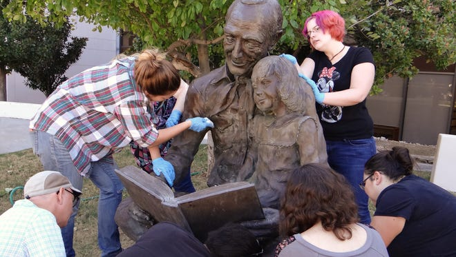 """Students in NMSU's museum conservation techniques class restore """"The Joy of Learning"""" sculpture."""