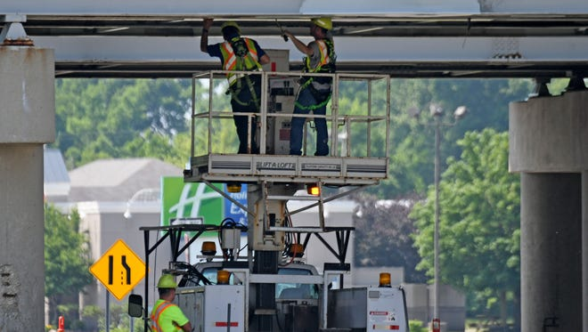 ODOT workers stay cool in the shade as they do maintenance work on the US 30 overpass at Ohio 4 on Monday.