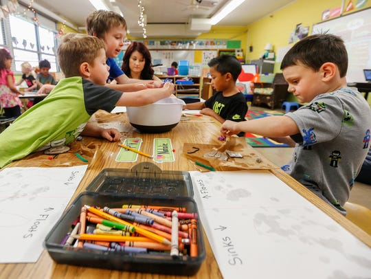 Andrea Estes, center, helps students, from left, Mason