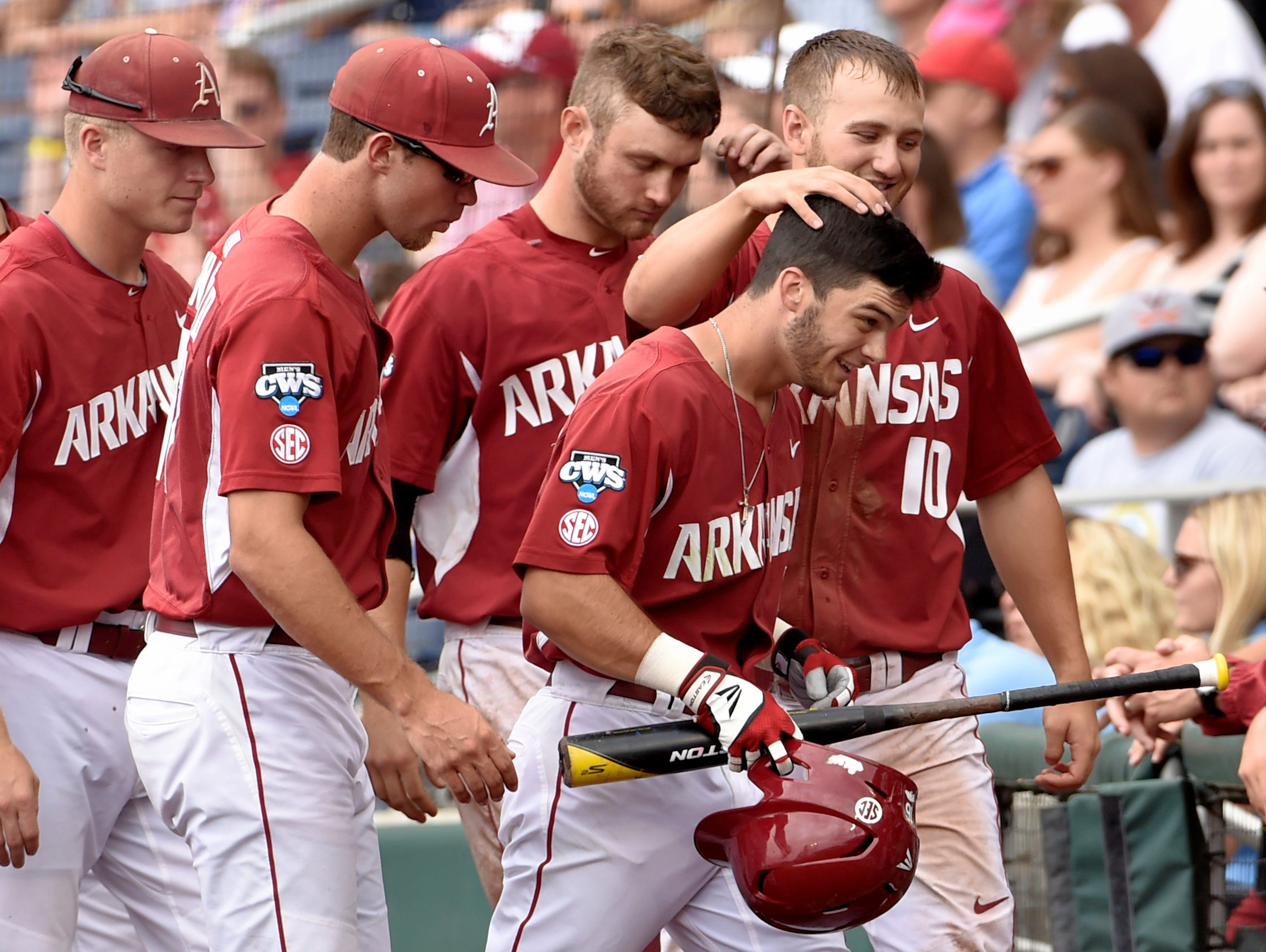Arkansas' Andrew Benintendi, bottom right, is greeted at the dugout by Joe Serrano (10) after he hit a solo home run against Virginia in the fifth inning.