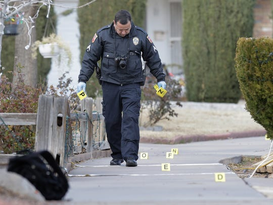 An officer with the criminalistics department marks evidence after a shooting Thursday in the 10300 block of Pasadena Circle.
