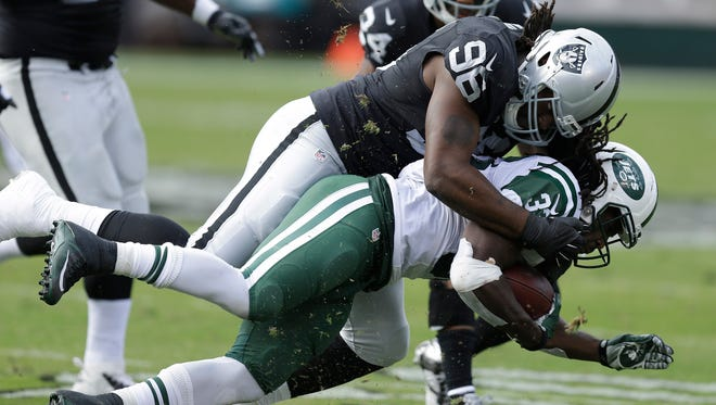 Oakland Raiders defensive end Denico Autry (96) tackles New York Jets running back Chris Ivory (33) during an NFL football game in Oakland, Calif., Sunday, Nov. 1, 2015. (