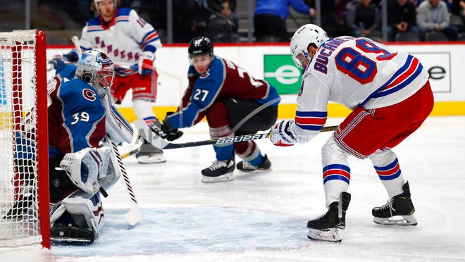 Avalanche goaltender Pavel Francouz, left, stops a shot off the stick of Rangers right wing Pavel Buchnevich during the second period