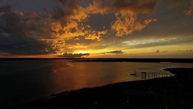 Stunning colors over Barnstable Harbor as storm clouds advance over the setting sun.