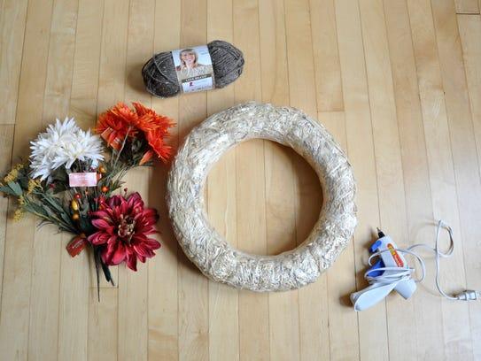 Make a fall wreath using yarn and silk flowers.
