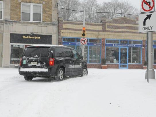 A taxi turns from Washington Street onto Orange Road