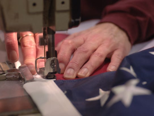 An American flag being sewed together with the stripes