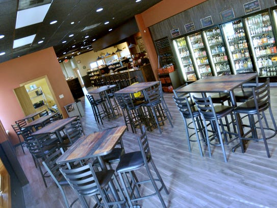 Craft Beer Cellar has a bar and tabletop seating inside,