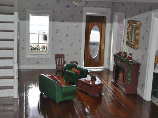 The dollhouse features a holiday theme.