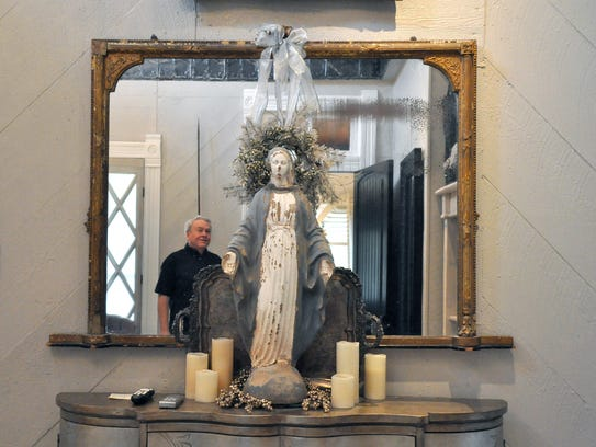 Terry Browder, owner of the Abilene Landmark boutique hotel, is reflected in a mirror behind a reclaimed Madonna statue on a dresser in the Luxe Room. The repurposed Victorian house will be part of the Abilene Woman's Club Holiday Tour of Homes.