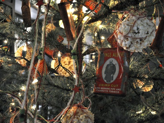 Red Prince Albert tobacco tins and popcorn ball ornaments adorn a Christmas tree at Abilene Landmark.