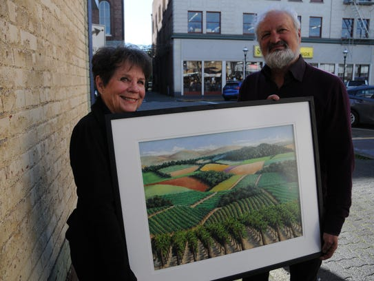 Lorraine Dye, left, and Roy John hold one of Dye's pastel paintings of a vineyard that will be on display during a First Wednesday reception this week.