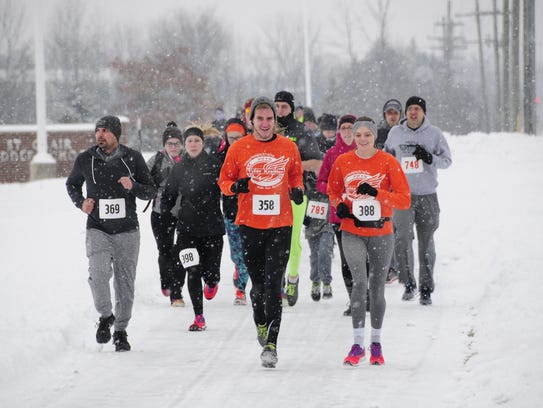 A pack of racers runs through the snow Saturday, Feb.