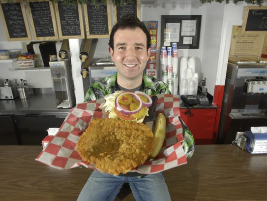 Brad Magg holds a pork tenderloin sandwich inside his Goldie's Ice Cream Shoppe in Prairie City. Register file photo