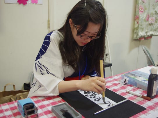Fusako Kurohashi writes a Japanese message for a visitor