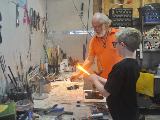 Cooper Noble, 8, creates a pendant with the help of