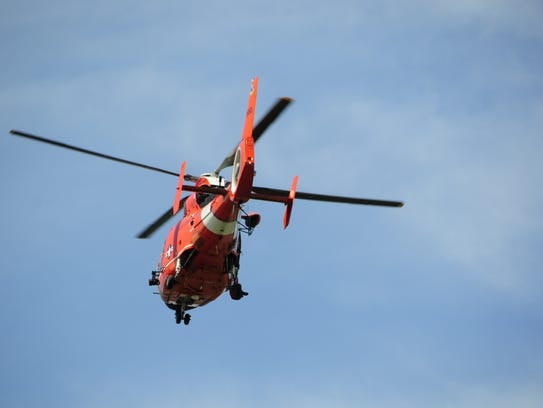 A U.S. Coast Guard helicopter looks for two people