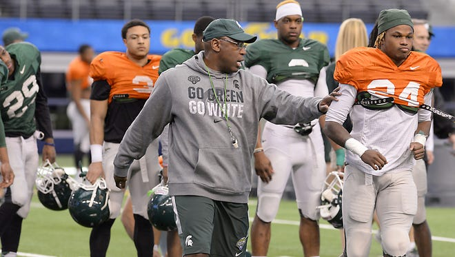 MSU secondary coach Harlon Barnett - promoted to co-defensive coordinator after Thursday's Cotton Bowl - works with his defensive secondary as the Spartans  practice Sunday at AT&T Park in Arlington, Texas.