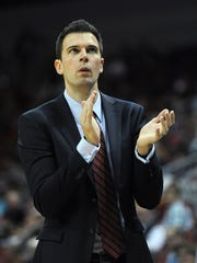 David Padgett claps on the Louisville sideline during the 2017-18 season.