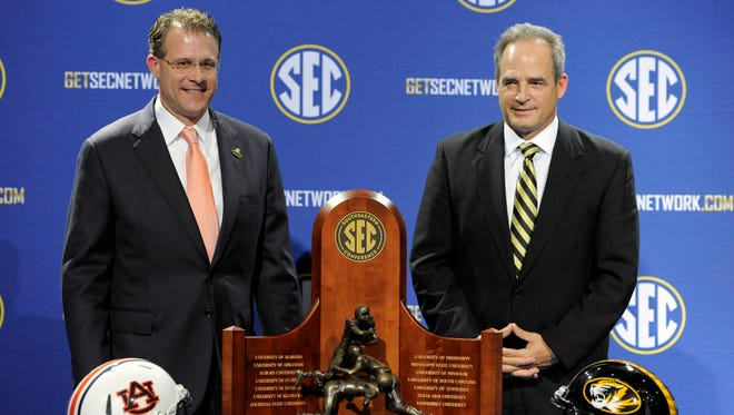 Auburn coach Gus Malzahn poses with the SEC Championship trophy on the day before the league's title game Friday.