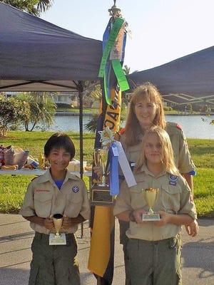 Alejo Ruiz-Vallejo, James Burns and Melanie Burns, Boy Scout Troop 234 Leader are seen with their tropy and troop flag.