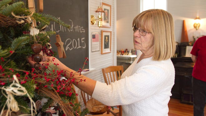 """Lin Millar, a member of the Brighton Area Historical Society board of directors, was among others from the society decorating the Lyon School for their upcoming event """"Old Time Christmas with Santa and Mrs. Claus."""""""