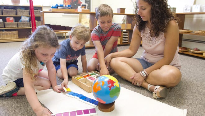 Leann Chamberlain, right, works with her three children, from left, 5-year-old Brooklyn, 3-year-old Caleb and 6-year-old Cruze in a pre-primary classroom at the soon-to-open Brighton Montessori school owned by Chamberlain.