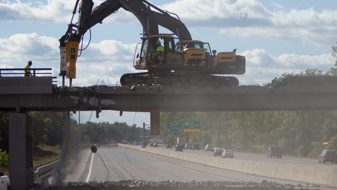 Michigan Department of Transportation crews work to demolish the Pleasant Valley overpass over the eastbound side of Interstate-96 Thursday, Sept. 28, 2017 after a semitruck struck the overpass the previous afternoon.