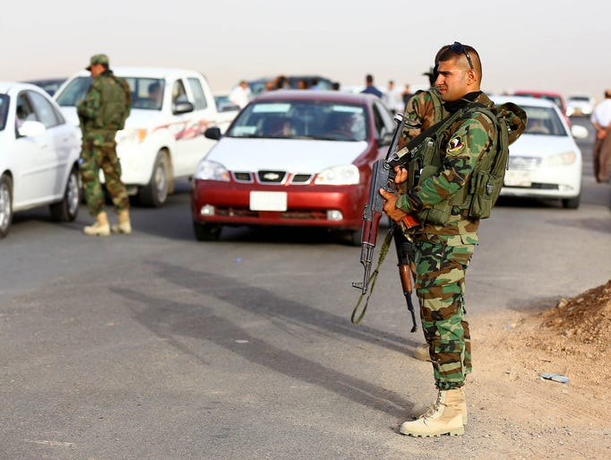 Kurdish police officers stand guard while refugees from Mosul enter Irbil.