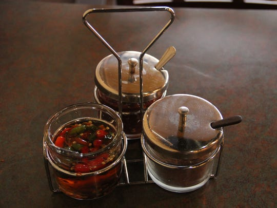 Fish sauce, the residual liquid from pressed anchovies, is available at the table in a jar with floating chilies.
