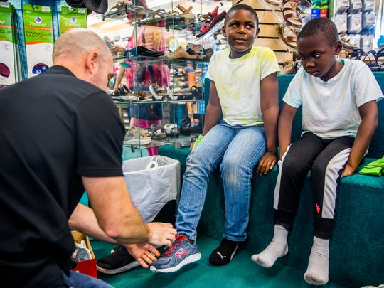 Incoming second-graders Clayton Cadostin, left, and Jamison Etienne, both of Immokalee, try on a pair of shoes at Snyderman's Shoes of Naples on Tuesday, July 10, 2018. Throughout this week, 250 kids from the Guadalupe Center in Immokalee will receive a new pair of shoes for the upcoming school year. This annual event is done through a partnership with Snyderman's Shoes and Laces of Love, a nonprofit that provides new shoes to low-income kids in Collier and Lee counties.