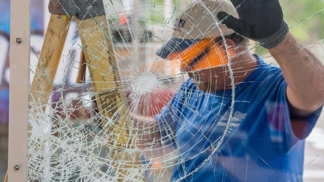 Brad Weston of Pekin Glass & Mirror works at removing a smashed pane of laminated glass Monday, June 1, 2020 at the Boost Mobile store, 3102 N. Gale Avenue, in Peoria.