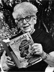 "Marjory Stoneman Douglas with her landmark book, ""Everglades: The River of Grass."""
