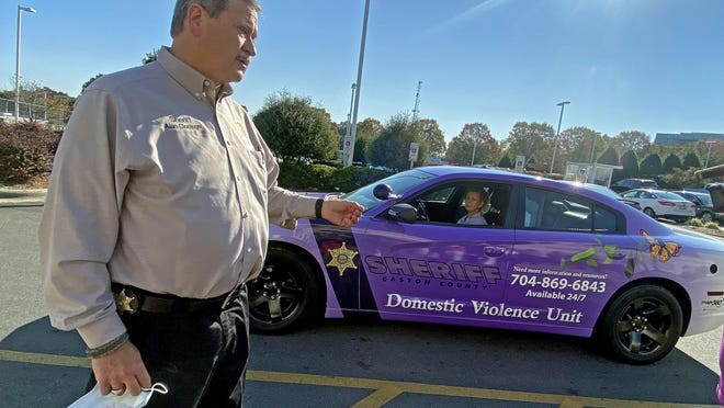Gaston County Sheriff Alan Cloninger shows off the patrol car that will advertise their services to victims of domestic violence. He was speaking at a press conference held Wednesday, Oct. 7, 2020, at the Gaston County Sheriff's Office.