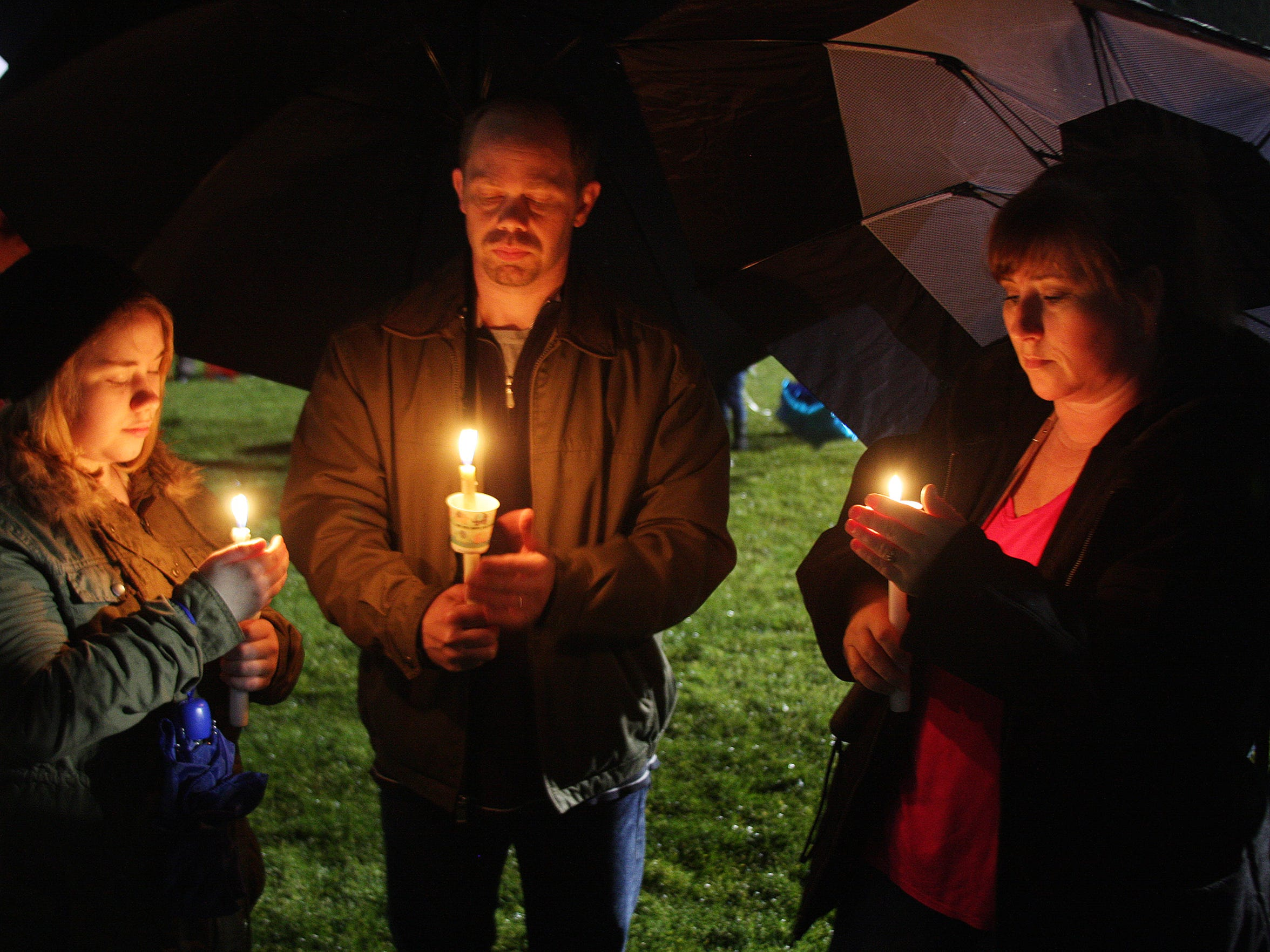 Cassie, Tim, and Carrie Stevens attend the candlelight vigil in honor and rememberance of Sabrina Almaraz and Kaleigh Woodman Sunday evening at Pennfield High School Football Field