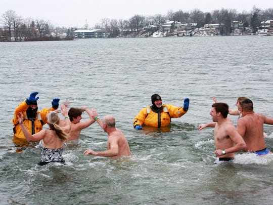 Deputy Andy Erard of the Marine Patrol and retired Lt. Bill Burgess receive high-fives from those who were able to get far enough in the cold Goguac Lake waters during the annual New Year's Day Splash.