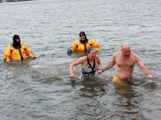 Running through the cold Goguac Lake waters back to shore during the annual New Year's Day Splash are Kellie LaDuke and Brian Hoffman.