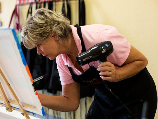 Terry Evans, of Naples, works on her painting at Painting