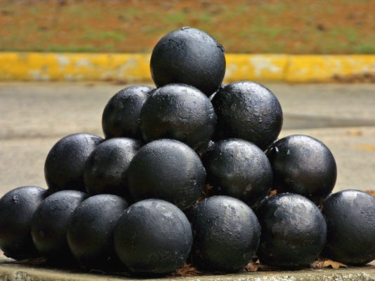 A pile of thirty cannonballs stacked on top of each other